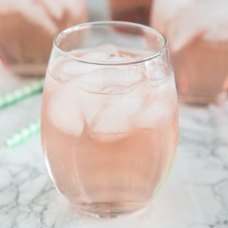 A close up of a wine glass with rose wine spritzer
