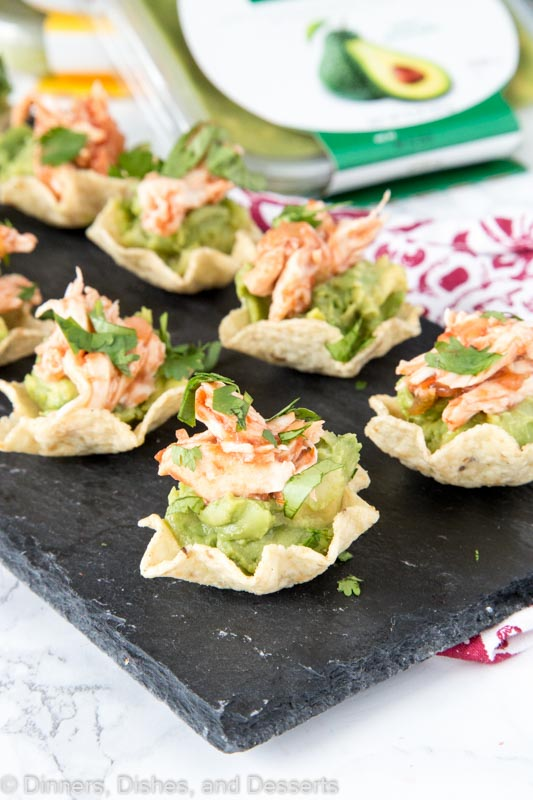tortilla chips topped with avocado and spiced chicken on a tray
