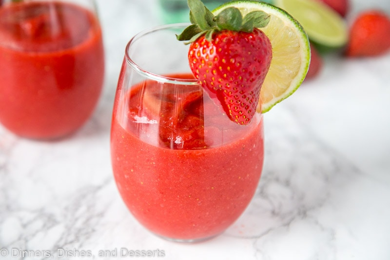 A glass of frozen strawberry daiquiri with a strawberry and lime slice