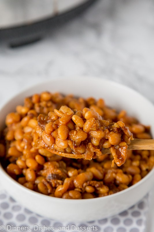 A bowl of food on a plate, with Bean and Baked beans