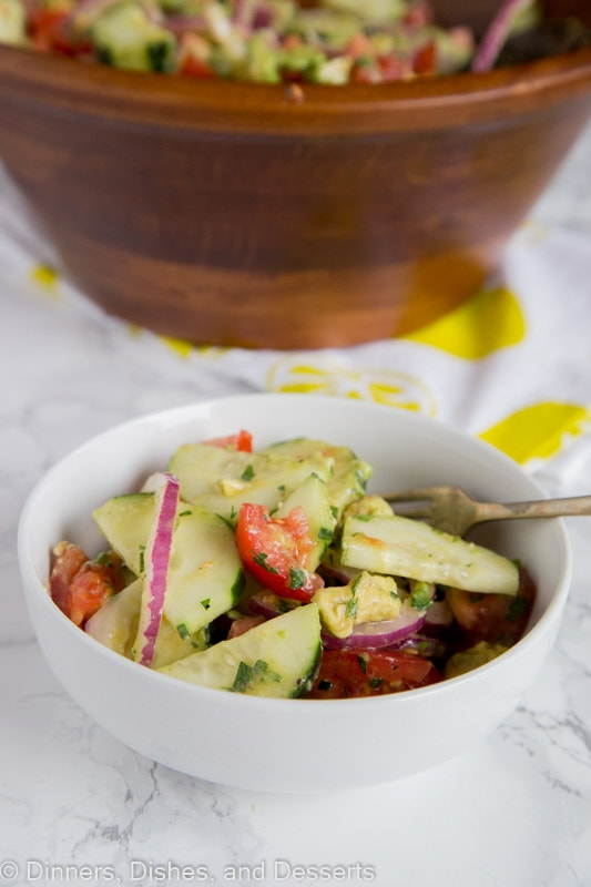 A close up of a bowl of food on a plate, with Salad and Cucumber