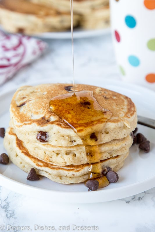 banana pancakes with chocolate chips stacked on a plate with syrup