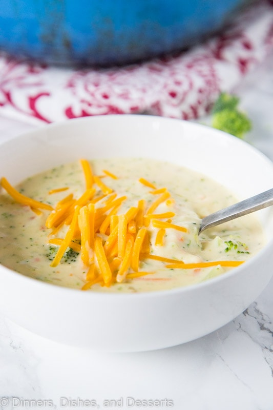 A bowl of broccoli cheese soup with spoon