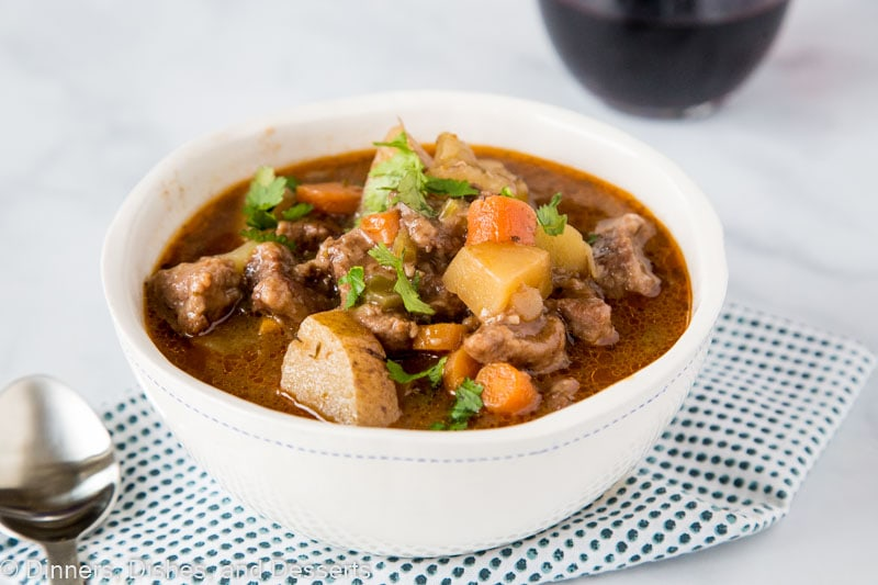 A bowl of food on a plate, with Stew and Beef