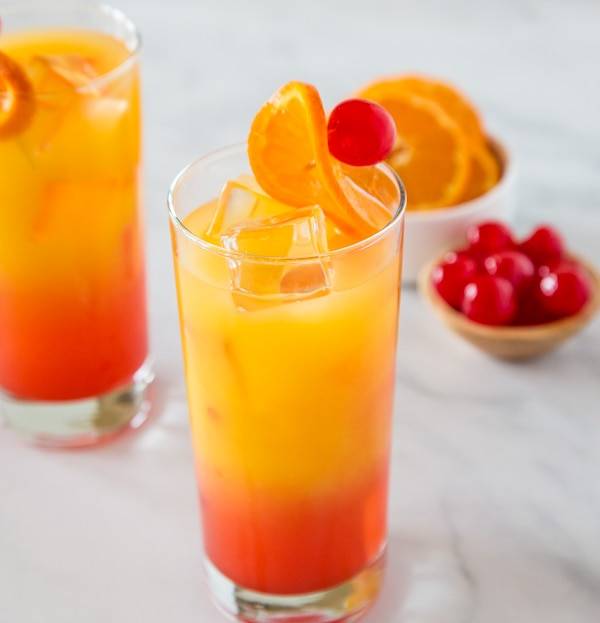 A glass of orange juice next to a bowl of cherries
