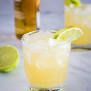 A glass of margarita with bottle of beer in the background with Margarita