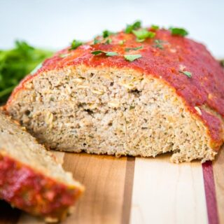 A slice of meatloaf sitting on top of a wooden cutting board, with Dinner and Meatloaf
