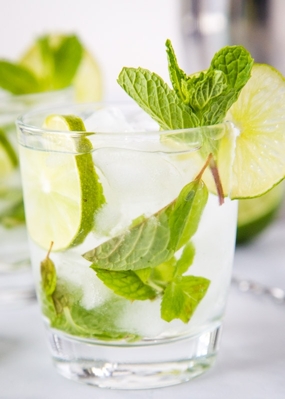 A glass cup on a table, with Mojito and Lime