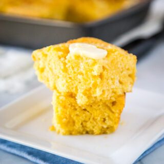 A piece of cornbread with butter on a plate, with Bread and Cornbread