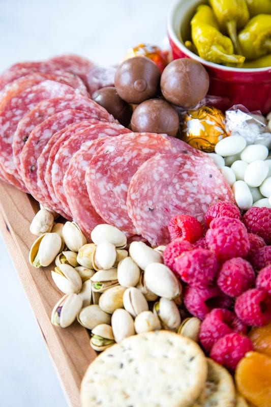 Italian dry salami, raspberries, pistachios on snack board