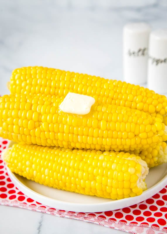 pressure cooker corn on the cob stacked on a white plate with pat of butter on top