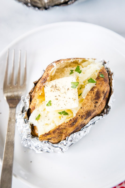 cut open baked potato with butter and chives