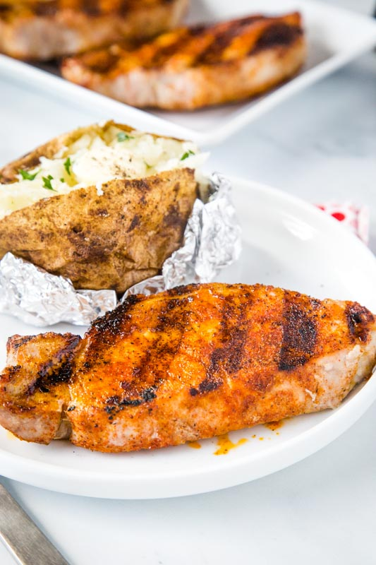 grilled bonless pork chop on white plate with baked potato