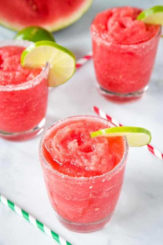 homemade watermelon flavored margaritas in glasses with slices of lime
