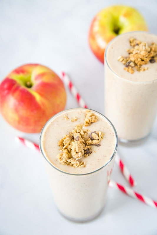 apple smoothie in a glass with an apple and straw next to it