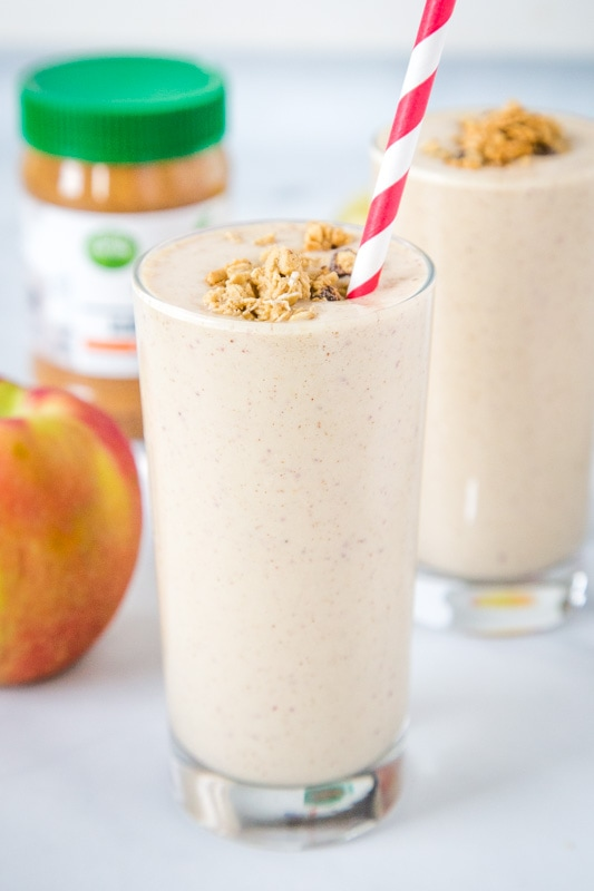 Apple smoothie with granola in a glass with a straw