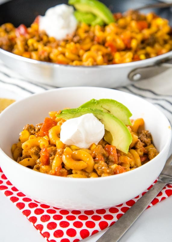taco pasta skillet with avocado and sour cream in a white bowl
