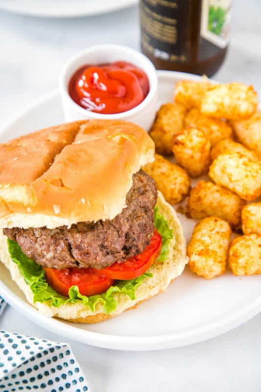 hamburger on bun with tater tots on a plate