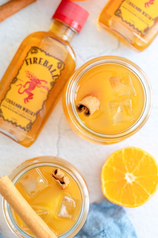 apple cider drink in glasses with bottle of fireball near by