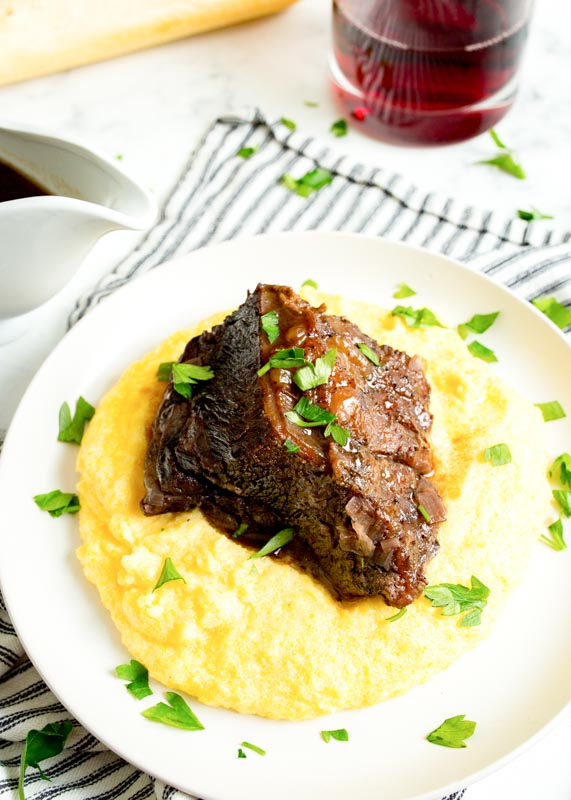 braised beef short ribs over polenta on a plate