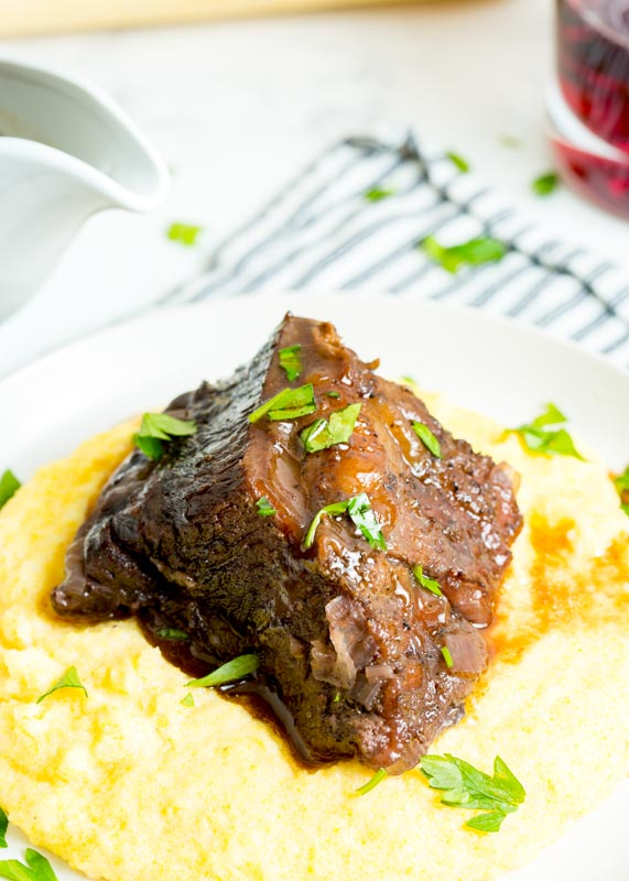 polenta on a plate with beef rib over it
