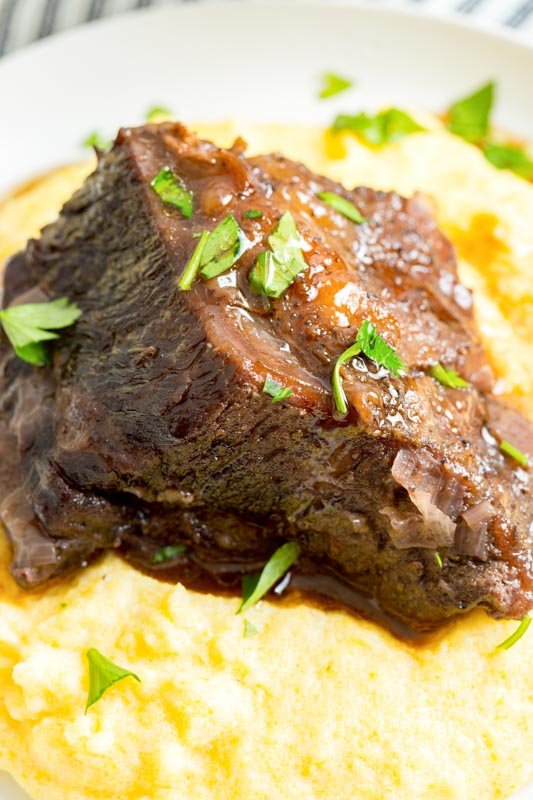 close up cooked beef rib sitting on polenta