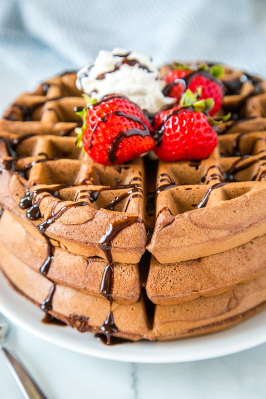 chocolate waffles topped with strawberries and chocolate sauce
