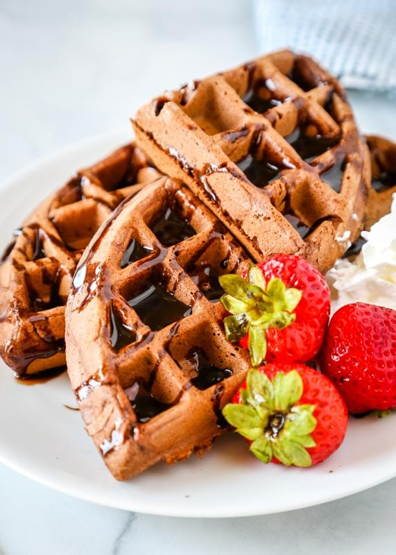 pieces of chocolate waffle with strawberries on a plate