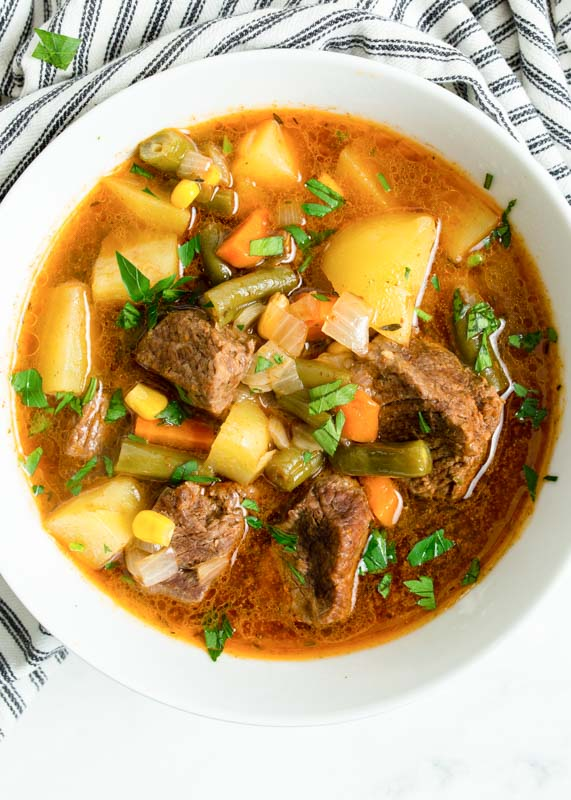 vegetables in beef in a soup in white bowls