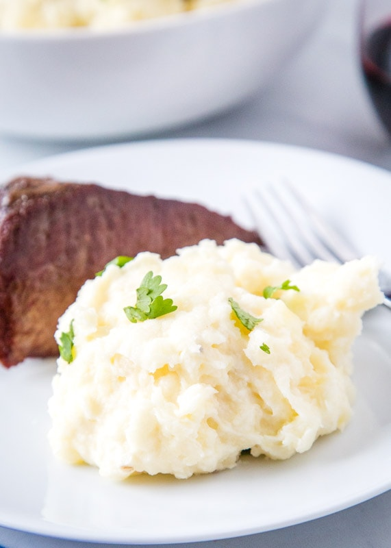 scoop of mashed potatoes on a plate with steak