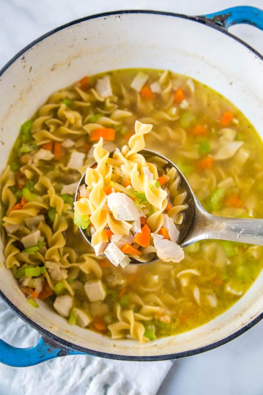 turkey soup in a pot with a ladle scooping out soup