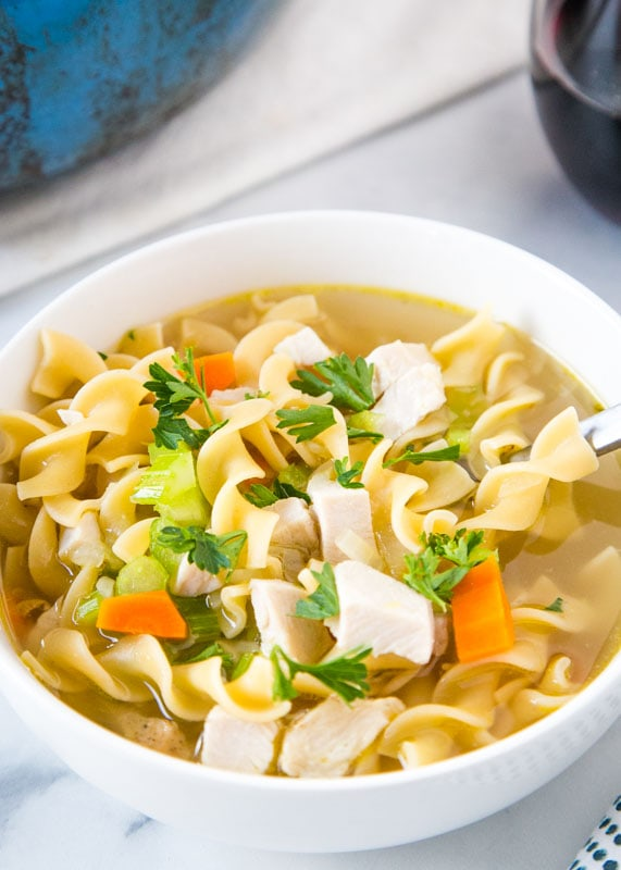 leftover turkey soup in a bowl topped with parsley