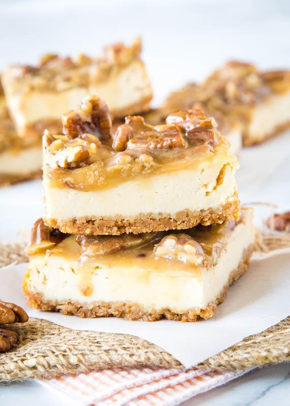 praline cheesecake bars staked on white paper