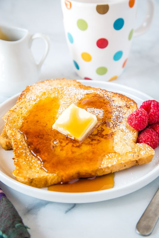 sourdough french toast with syrup on white plate