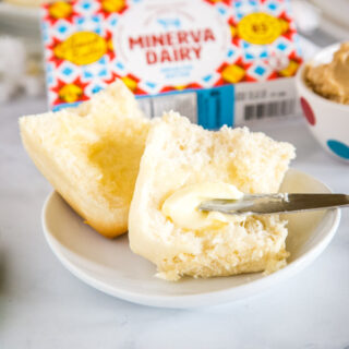cropped image of butter being spread on a roll