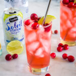 cropped image of cranberry spritzer in glass with fresh cranberries on top