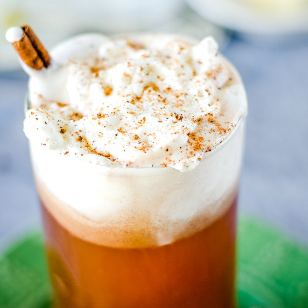 cropped image of hot buttered rum in glass with whipped cream