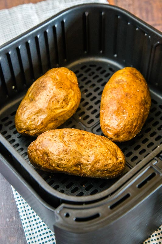 cooked baked potatoes in the air fryer basket