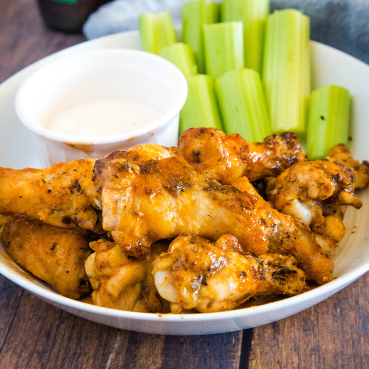 cropped image of buffalo chicken wings on plate with ranch and celery sticks
