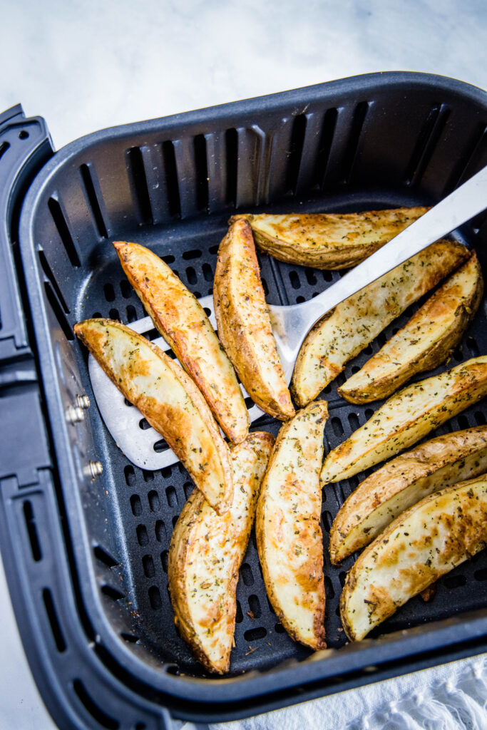spatula removing cooked potato wedges from air fryer