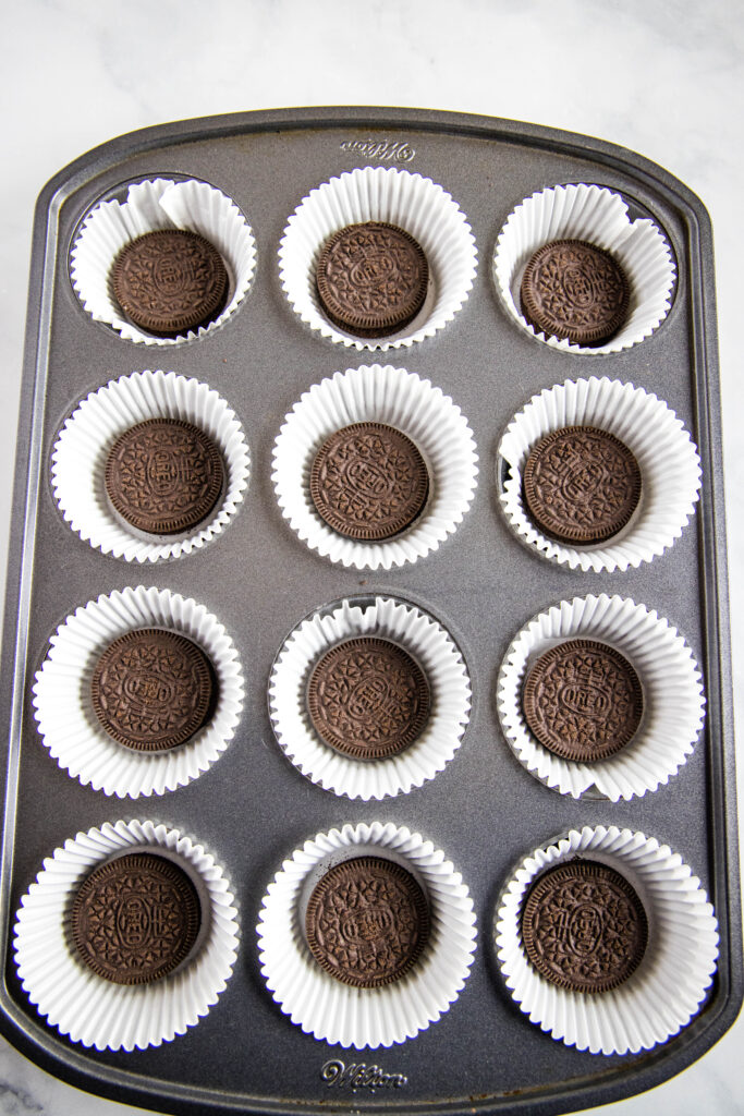 muffin tin lined with paper liners and an oreo in each cup