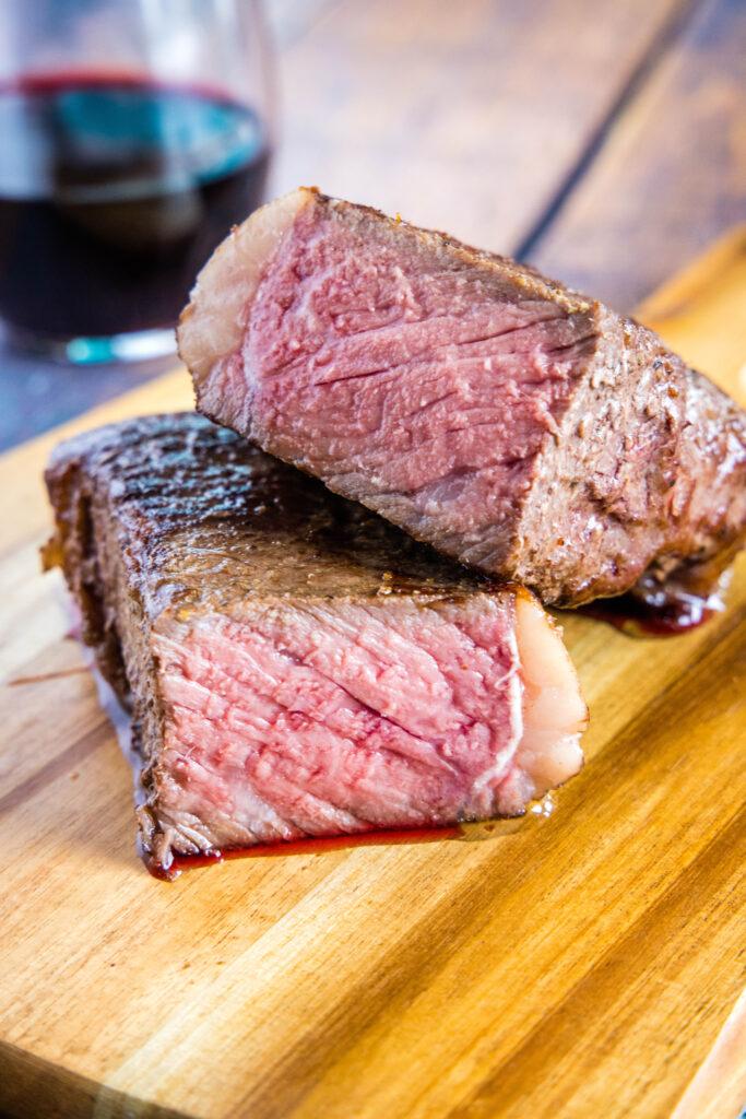 steak cut in half on cutting boar