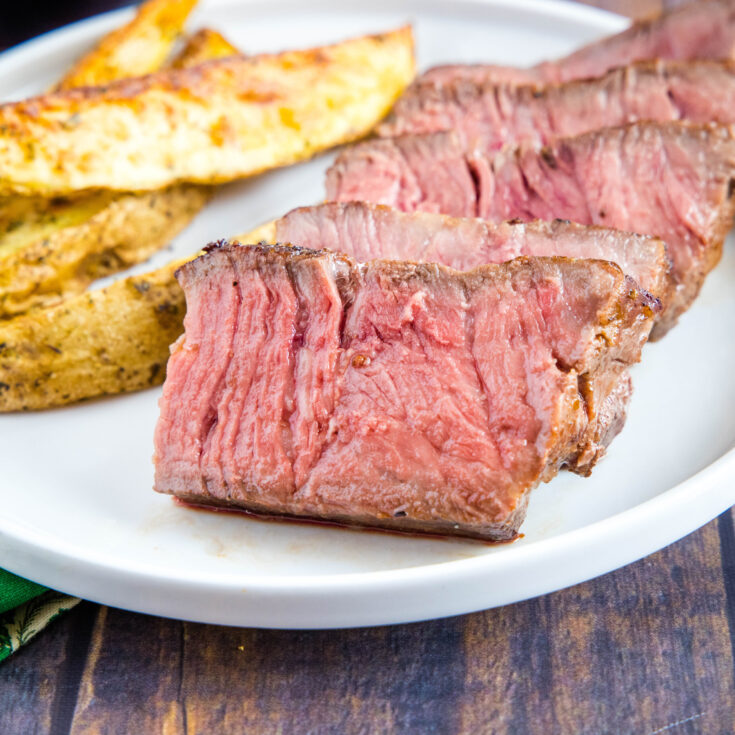 cropped sous vide cooked steak sliced on a plate