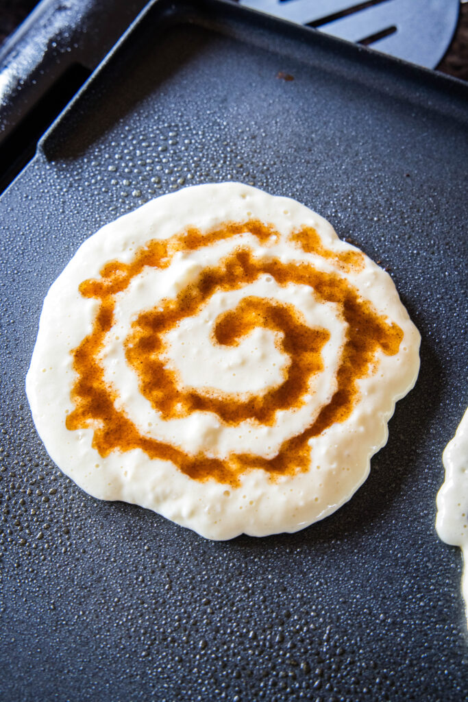 pancake on griddle with cinnamon swirl