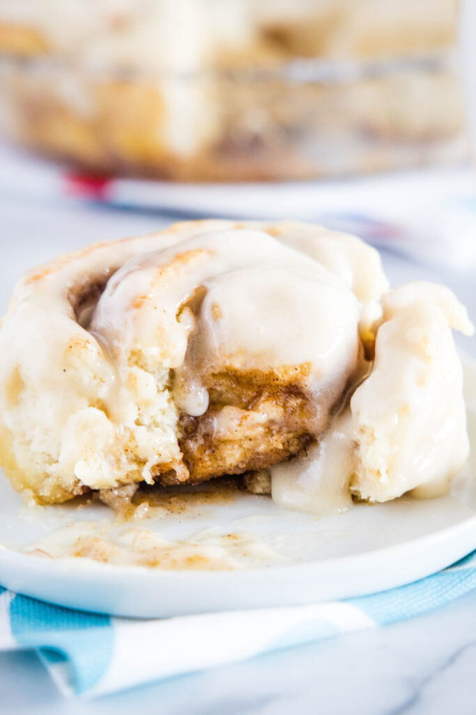 cinnamon roll on a plate with bite missing