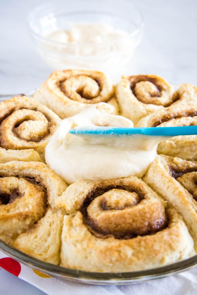 spreading frosting on cinnamon rolls