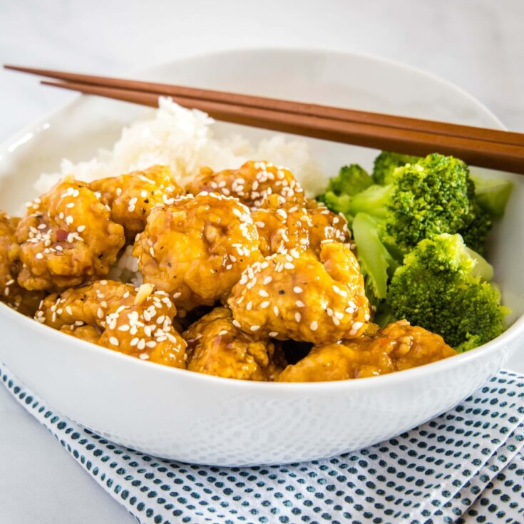 cropped sesame chicken picture with broccoli in white bowl