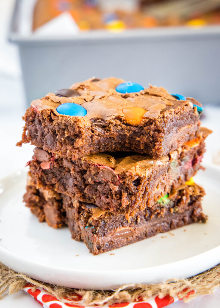 M&M brownies stacked with a bite out of one