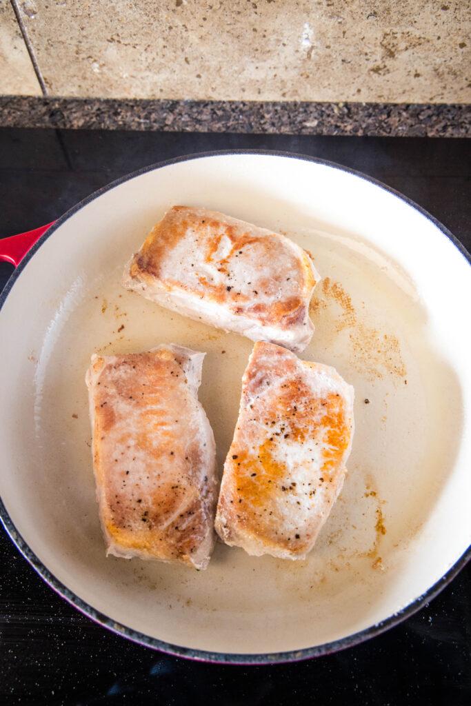 pork chops browning in a skillet