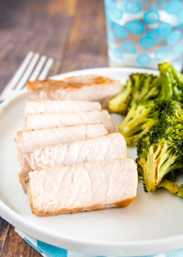 sliced pork chop on plate with broccoli